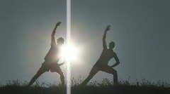 Woman and man stretching infront of sunset Stock Footage