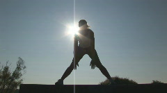 Woman stretching at sunset - silhouette of straddle Stock Footage
