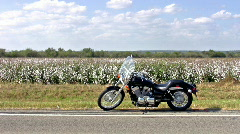 Motorcycle parked in front of cotton field HD Stock Footage