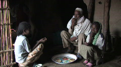 Ethiopia: Father and two daughters eat - stock footage