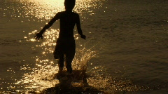 BOY RUNNING INTO LAKE 720 24p - stock footage