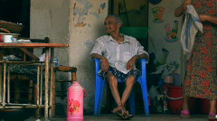 An old man sitting on a chair in Chengdu, China - stock footage