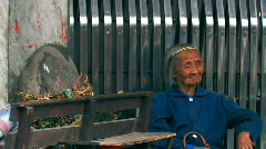 An old lady sitting on a bench in Chengdu, China Stock Footage