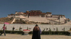 An old woman is praying outside Potala Stock Footage