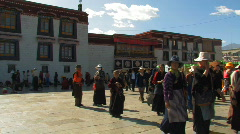 Tibetan people walking and praying outside Jokhang temple in Lhasa, Tibet Stock Footage