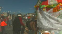 Woman praying close to praying flags outside Jokhang temple in Lhasa, Tibet Stock Footage