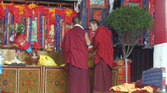 2 Buddhist Monks talking inside Jokhang Temple Tibet Stock Footage