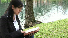 Girl outside reading bible Stock Footage