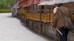 A limping tibetan man spinning prayer wheels Stock Footage