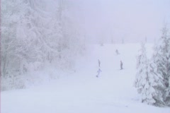 Skiers comming down foggy frozen slope Stock Footage