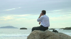 Businessman with mobile phone on the beach Stock Footage