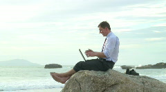 Businessman with laptop on the beach - stock footage