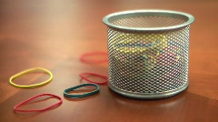 Colored Rubber bands falling onto Office Desktop - stock footage
