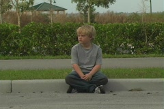 Boy at Roadside Curb Stock Footage