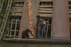 Two boys put planks on canoes in Aceh, Indonesia Stock Footage