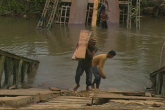 Young man carries planks up broken bridge Stock Footage