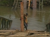 Stock Video Footage of Young man carries planks up broken bridge
