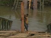 Young man carries planks up broken bridge Stock Footage