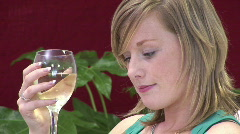 Attractive Woman relaxing on sofa with a glass of whitewine Stock Footage
