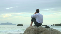 HD: Businessman with cell phone sitting on a rock at the sea - stock footage