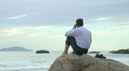 Stock Video Footage of HD: Businessman with cell phone sitting on a rock at the sea