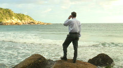 HD: Businessman with cell phone on the beach Stock Footage