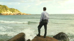 HD: Businessman standing on a rock at the sea Stock Footage
