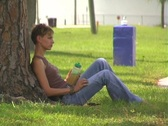 Stock Video Footage of Lovely Young Woman Relaxes in the Shade with a Health Drink