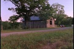 Minivan passes old barn - stock footage