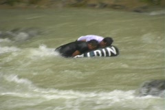 Teenagers fall off tube in river Stock Footage