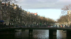 Pedestrians move across bridge in scenic Amsterdam - stock footage