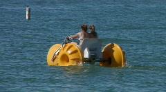 Girls peddling watercraft in ocean Stock Footage
