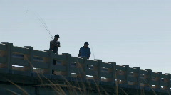 Men fishing from ocean pier Stock Footage