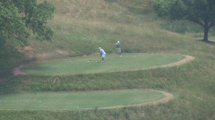 golfers playing in hills zoom out GA - stock footage