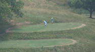 Stock Video Footage of golfers playing in hills zoom out GA