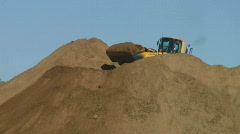 Front loader builds dirt pile Stock Footage
