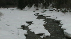 Zoom in shot of mountain stream flowing over rapids with snow covered banks - stock footage