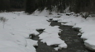 Zoom in shot of mountain stream flowing over rapids with snow covered banks Stock Footage