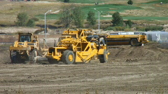 Bulldozers and scrapers move dirt - stock footage