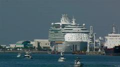 Small boats cruise harbor among big ships Stock Footage