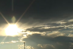 Sun with lens flare from behind storm clouds - stock footage