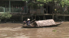 Woman steers her boat along one of the many waterways of the Mekong Delta Stock Footage