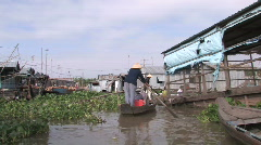 Tourists ride through a typical houseboat village in the Mekong Delta Stock Footage