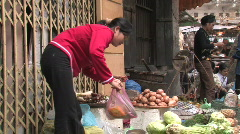 Man buys vegetables from a sidewalk vendor in Hanoi, Vietnam Stock Footage