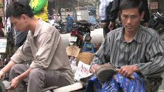 Vietnam: Sidewalk Shoe repair CU Stock Footage