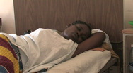 Woman lies in her hospital bed on an AIDS ward in a hospital in Kenya Stock Footage