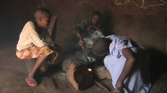 Girls cook over an open fire in their home in Tanzania, Africa - stock footage
