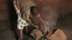 Girl starts a fire to cook a meal in Tanzania, Africa - stock footage