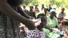 Stock Video Footage of A woman makes her weekly payment in a small loans program in Kenya