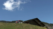 Stock Video Footage of Red tractor in the moutain, blue sky, one cloud and a chalet
